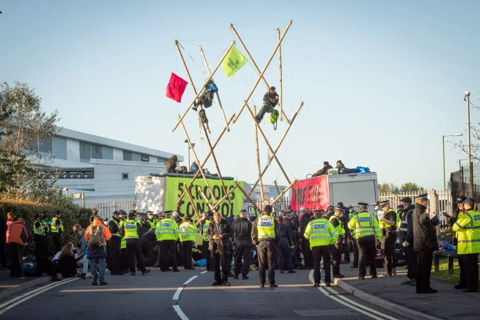 Extinction Rebellion block Rupert Murdoch printworks with two amazing bamboo structures, a person atop each, many police around bamboozled