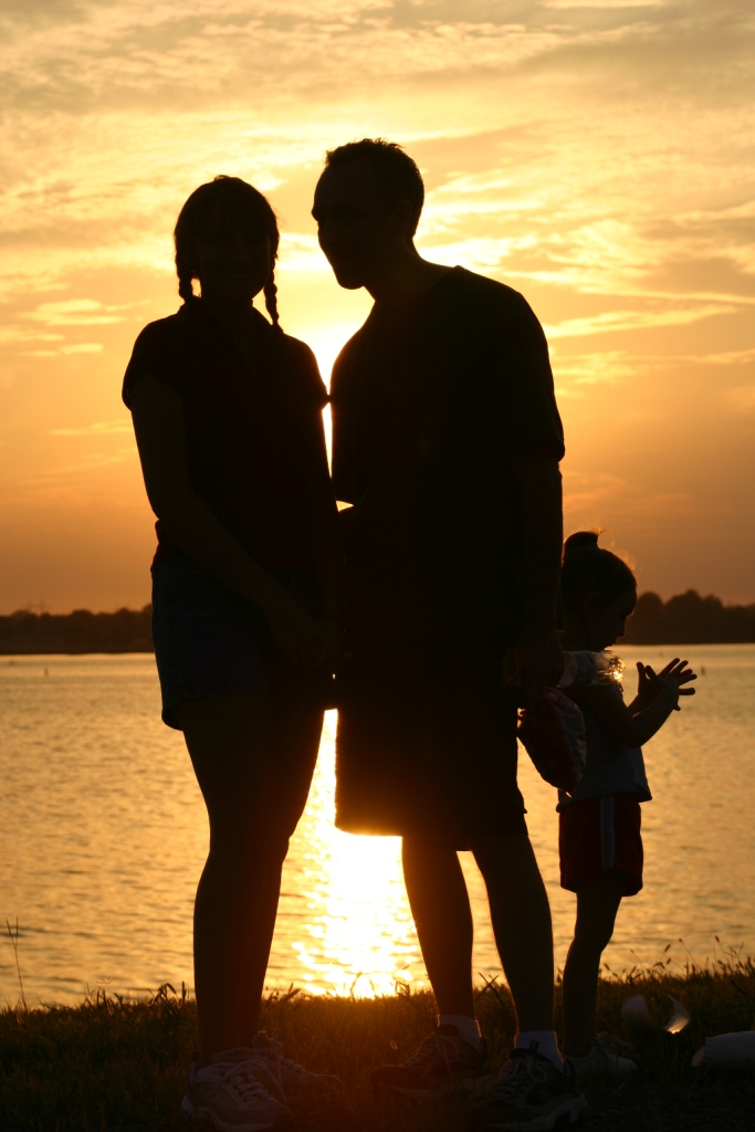 Family silhouetted by sun